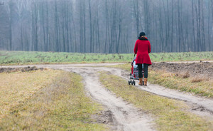 Photo of woman walking with stroller by sandy rural road