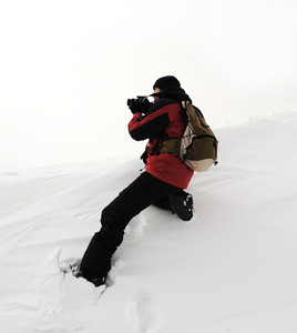 Photographer in extreme conditions getting picture of mountain view