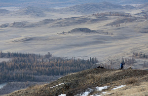 Photographer standing atop a vast, rolling hill
