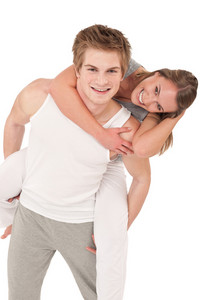 Piggyback - Young sportive smiling  couple  wearing fitness clothes on white background