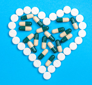 Pills in heart shaped on blue background