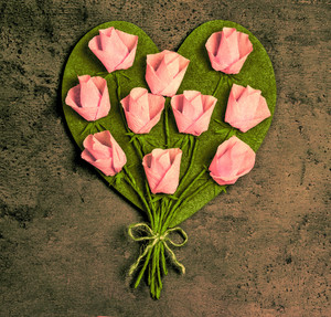 Pink roses in a heart shape on vintage wooden background