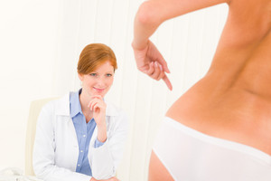 Plastic surgery consultation female doctor patient point skin on hips
