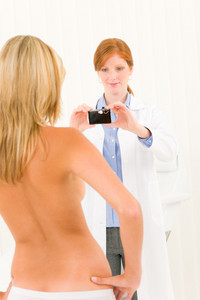 Plastic surgery female doctor take picture of woman patient breast