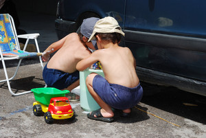 Playing around the car and cleaning, children in summertime