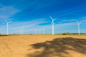 Plowed fields and wind farm. Beautiful landscape with blue sky over plowed field and windmills.