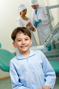 Portrait of happy boy in dentist room on background of two doctors