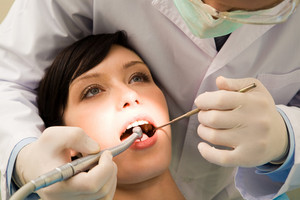 Image of young woman keeping her mouth open while dentist examining it