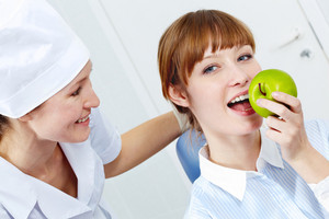 Portrait of pretty woman eating a green apple with nurse near by