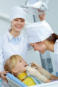 Image of little girl having teeth checked by doctor and assistant