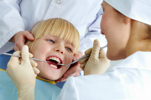 Image of little girl having her teeth checked by doctor and assistant