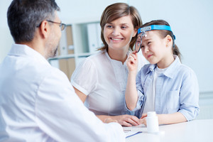 Cute girl and her mother consulting with the doctor in hospital