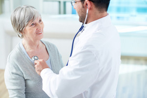Confident doctor examining his senior patient in hospital