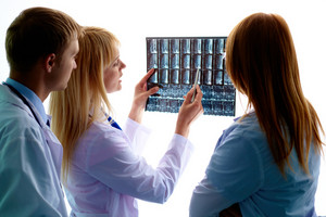 Portrait of young doctor showing and interpreting x-ray to colleagues