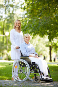 Pretty nurse walking with senior patient in a wheelchair in park