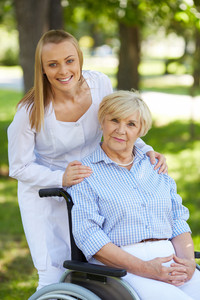 Pretty nurse and senior patient in a wheelchair looking at camera