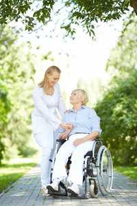 Pretty nurse walking with senior patient in a wheelchair in park