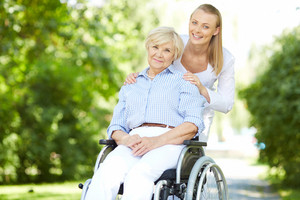 Pretty nurse and senior patient in a wheelchair looking at camera outside
