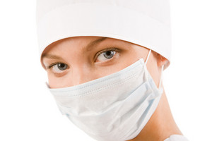 Face of nurse in sterile mask looking at camera over white background