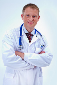 Portrait of cheerful doctor with stethoscope looking at camera and smiling
