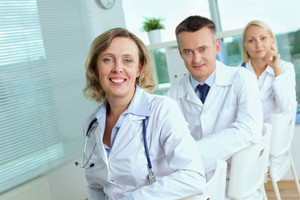 Portrait of three clinicians looking at camera with mature woman in front