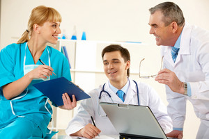 Photo of aged physician and young clinician looking at document in nurse's hand