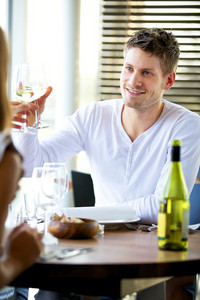 Portait of a man toasting with a glass of wine at a restaurant