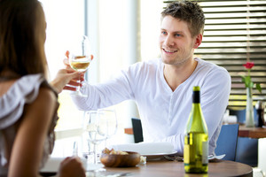 Portait of a romantic couple toasting with glasses of wine at a restaurant