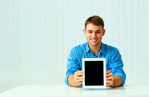 Portait of a young businessman shows the tablet computer screen at office