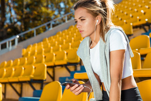 Portrait of a a young fitness woman holding smartphone on outdoors stadium