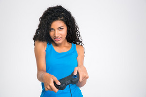 Portrait of a beautiful afro american woman playing in video game with joystick isolated on a white background