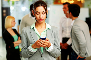 Portrait of a beautiful businesswoman using smartphone in front of colleagues