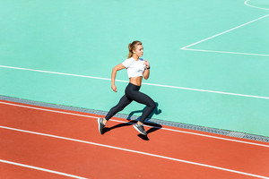 Portrait of a beautiful fitness woman running at stadium