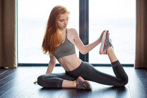 Portrait of a beautiful redhair woman stretching legs