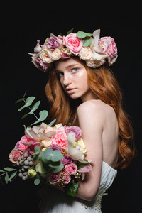 Portrait of a beautiful redhead woman posing with flowers over black background