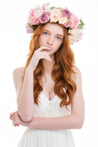 Portrait of a beautiful redhead woman with wreath from flowers on head standing isolated on white background