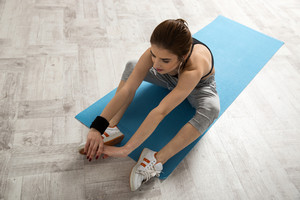 Portrait of a beautiful woman stretching on the yoga mat at gym