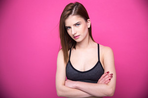 Portrait of a beautiful woman with arms folded over pink background