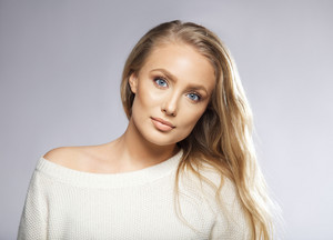Portrait of a beautiful young blond woman against grey background. Model has long blond hair, blue eyes and beautiful clean skin.