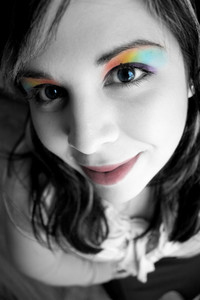 Portrait of a beautiful young womans face close up with rainbow eyeshadow makeup.  Shallow depth of field.