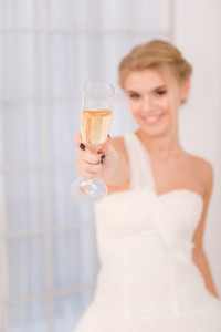 Portrait of a bride holding glass with champagne. Focus on glass