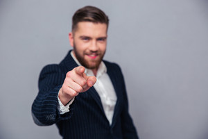Portrait of a businessman pointing finger at camera
