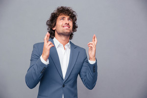 Portrait of a businessman praying with crossed fingers