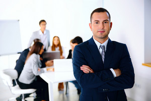 Portrait of a businessman standing in front of business meeting