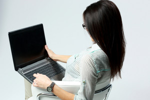 Portrait of a businesswoman using laptop on gray background
