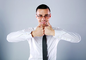 Portrait of a cheerful businessman standing with thumbs up on gray background