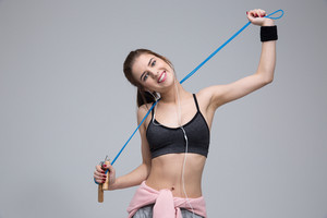 Portrait of a cheerful woman with jumping rope over gray background