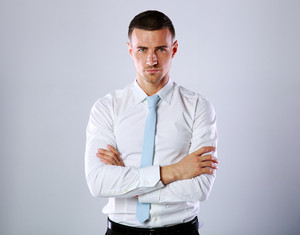 Portrait of a confident businessman standing with arms folded on gray background