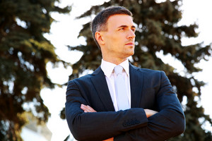 Portrait of a confident businessman standing with arms folded