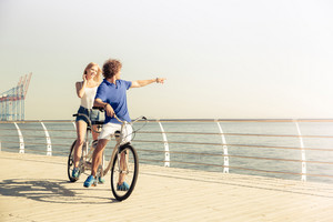 Portrait of a couple riding on tandem bicycle outdoors near the sea